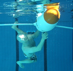 Diver in a pool with a robot.